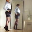 Stock Photo: Confident young businesswoman posing in front of mirror