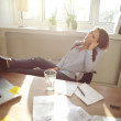 Relaxed businesswoman with legs on the desk — Stock Photo