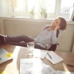 femme d'affaires décontractée avec les jambes sur le Bureau — Photo