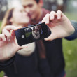 Romantic teenage couple taking self portrait — Stock Photo