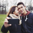 Young couple taking pictures using a smart phone — Stock Photo