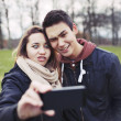 Funny teenage couple photographing themselves — Stock Photo #40697999