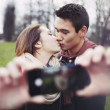 Lovely couple taking self portrait while kissing — Stock Photo #40698741