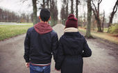 Teenage couple walking in park holding hands — Stock Photo
