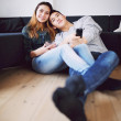 Relaxed teenage couple watching TV at home — Stock Photo