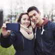 Cute young couple taking self portrait in the park — Stock Photo