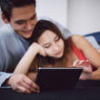 Romantic young couple lying on couch using tablet — Foto de Stock