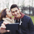 Loving teenage couple taking self portrait — Stock Photo