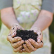 Old woman with a handful of compost — Stock Photo