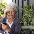 Senior woman looking at mobile phone — Stock Photo