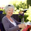 Senior woman in garden with a book — Stock Photo