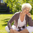 Senior woman sitting outdoors lost in thoughts — Stock Photo