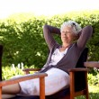 Elder woman resting in backyard garden — Stock Photo