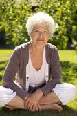 Beautiful senior woman sitting in her garden — Stock Photo