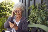 Senior woman looking at mobile phone — Stock Photo