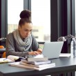 Woman using laptop for taking notes to study — Stok fotoğraf