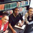 Confident young students at library using computer — Foto Stock