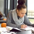 Young african american woman taking notes for her study — Foto de Stock