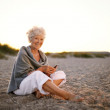 Senior caucasian woman with cell phone on the beach — Stock Photo #44139001