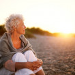 Old woman sitting on the beach looking away at copyspace — Stock Photo #44139013