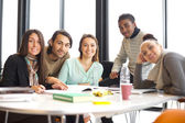 Happy young students at table studying together — Stock Photo