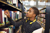 Young man looking for books at public library — Stok fotoğraf
