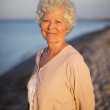 Beautiful old woman standing alone at the beach — Stock Photo