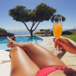Woman sunbathing along a pool with orange juice — Photo