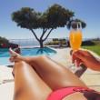 Woman sunbathing along a pool with orange juice — Stockfoto