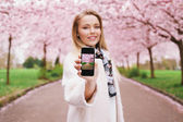 Young woman showing spring park picture on her mobile phone — Foto de Stock