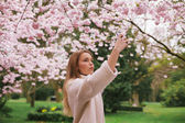 Attractive woman photographing flowers at the spring garden — Stock Photo