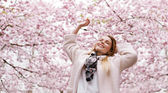 Happy young woman enjoying fresh air at spring blossom park — Stock Photo