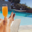Young lady with orange juice sunbathing at the poolside — Stok fotoğraf
