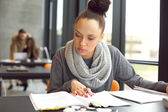 Female student studying in a library — Stock Photo
