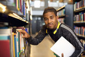 Young man getting books from a public library shelf — Stock Photo