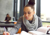 Young afro american woman doing assignments in library — Stock Photo