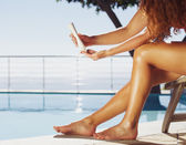 Women applying sun cream on legs — Stock Photo