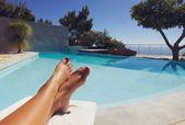 在游泳池边晒日光浴的年轻女子的脚 — 图库照片