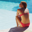 Young woman sitting on the edge of pool — Stock Photo #46214355