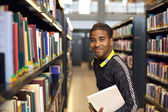 Young man in library for reference books — Stock Photo
