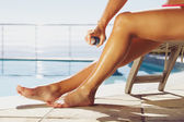 Woman applying suntan spray on her legs — Stock Photo