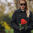 Young woman at graveyard with fresh roses — Stock Photo #46585681