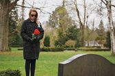 Woman grieving at cemetery holding flowers — Stock Photo