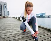 Fastening her shoelaces before the run — Stock Photo