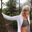 Beautiful young woman resting after jogging in a park — Stock Photo