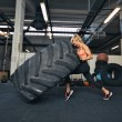Crossfit woman flipping a huge tire at gym — Stock Photo #48503625