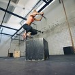 Fit woman is performing box jumps at gym — Stock Photo #48503713