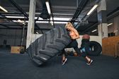 Crossfit woman flipping a huge tire at gym — Stock fotografie