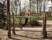 Fitness female doing parallel bar dips — ストック写真