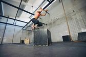 Fit frau führt box jumps in turnhalle — Stockfoto